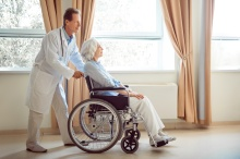 Rehabilitation process. Cheerful doctor helping positive and content senior patient in wheelchair